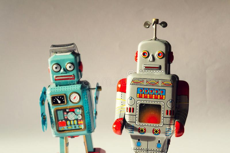 Two angry vintage tin toy robots, artificial intelligence, robotic drone delivery, machine learning concept. Two angry vintage tin toy robots, artificial royalty free stock image