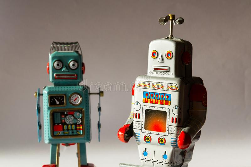 Two angry vintage tin toy robots, artificial intelligence, robotic drone delivery, machine learning concept. Two angry vintage tin toy robots, artificial stock photos