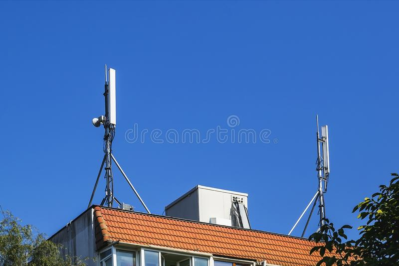Two antennas of cellular communication on an orange tiled roof of a multi-storey residential building against blue sky. Low angle view royalty free stock image