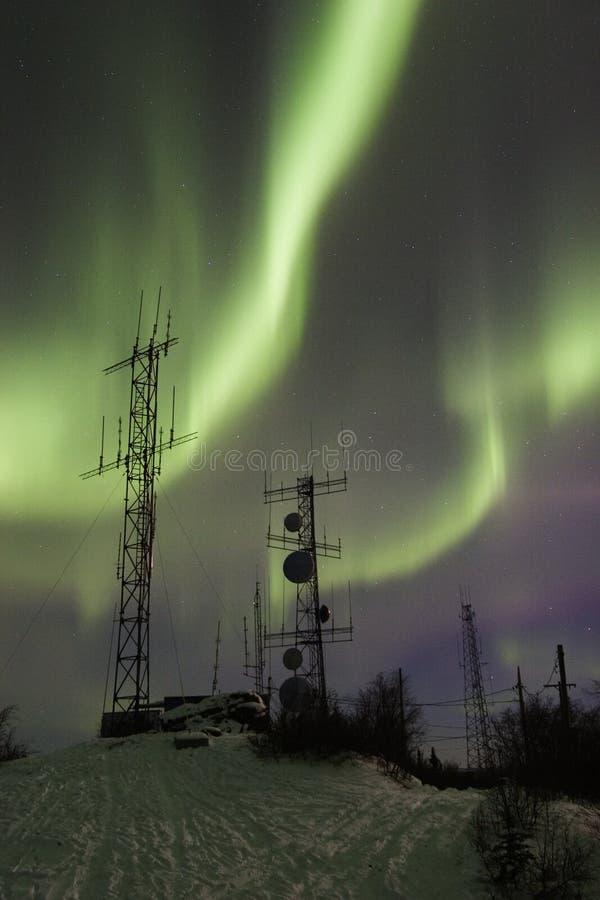 Two antennas under two aurora arcs stock image