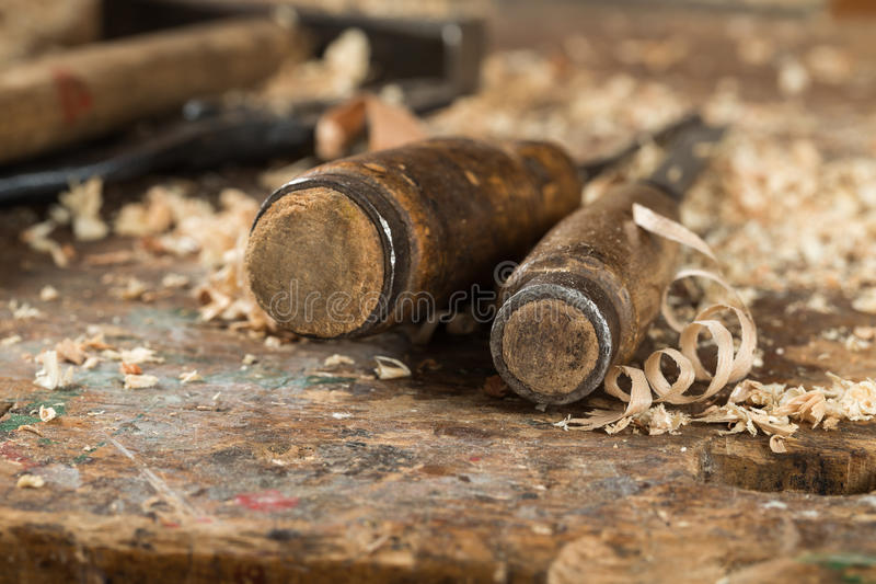 Two antique chisels. Composition of two antique chisels and wood chips on the working desk in wood workshop stock image