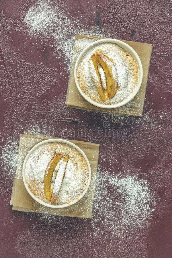 Two apple pies in ceramic baking molds ramekin with parchment  on dark red concrete table. Top view, flat lay stock image