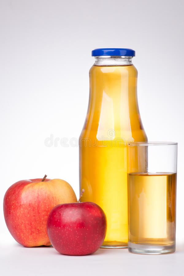 Two apples and a bottle of apple juice on white background.  royalty free stock image