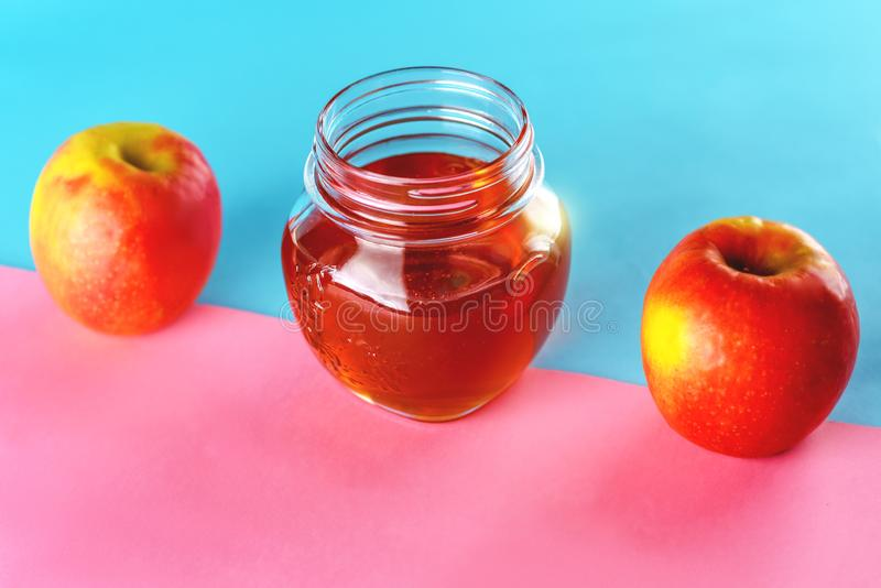 Honey and apples over blue pink background. royalty free stock photo