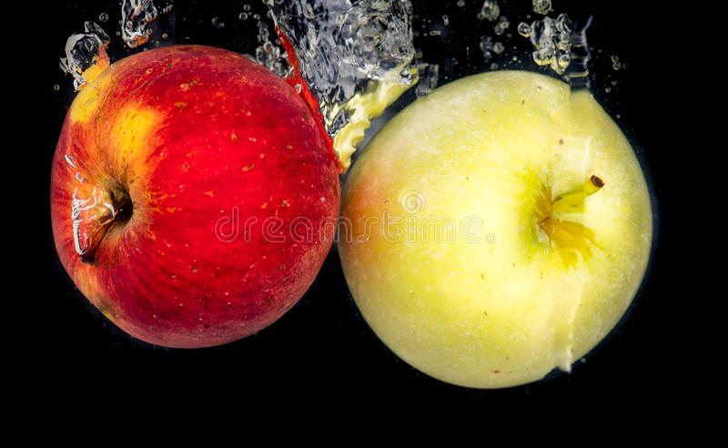 Two apples, red and green, thrown into the water on a black background royalty free stock photo