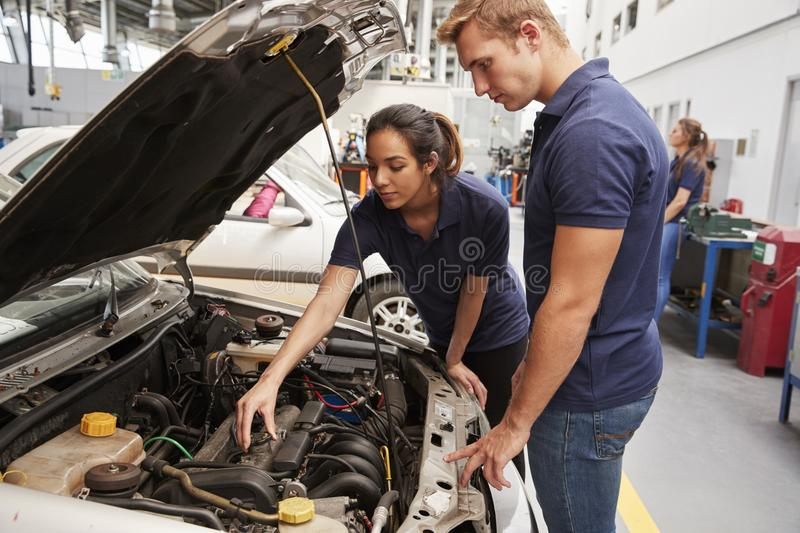 Two apprentice mechanics looking at the engine in a car royalty free stock photo