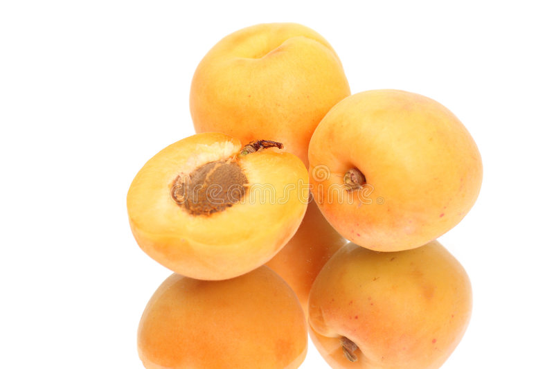 Two Apricots with halves. With reflection stock photo
