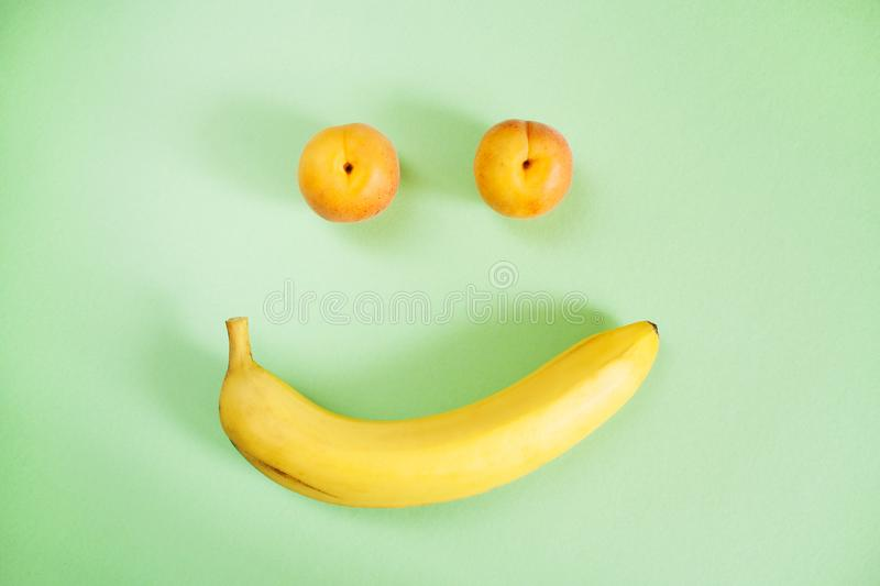 Two apricots and one banana on green background as smiley. stock image
