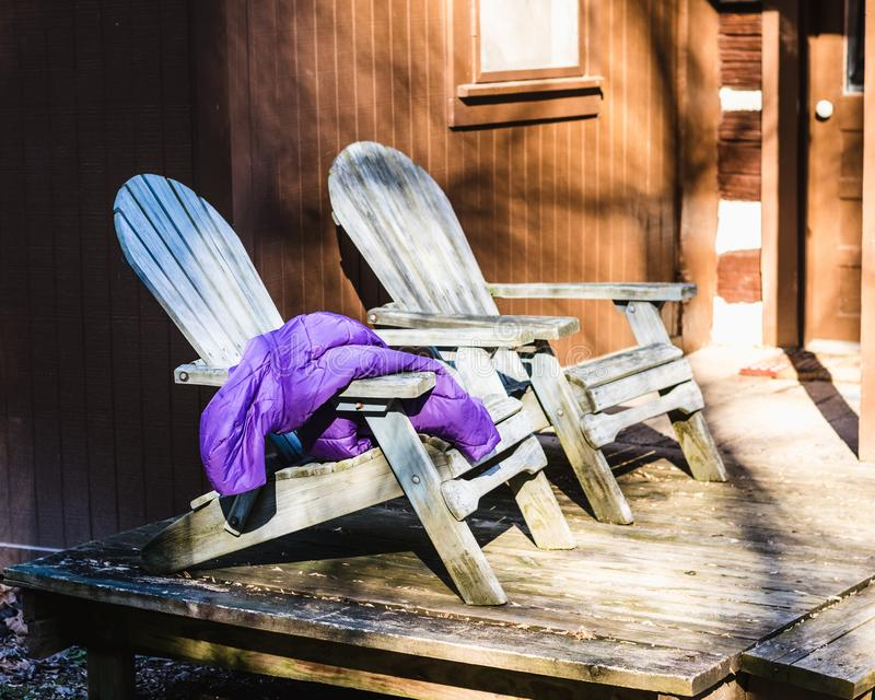 Two Aqua Adirondack Chairs on a Cabin Porch. Two aqua Adirondack chairs on the porch of an old cabin. Purple down winter coat draped over one of the chairs stock image