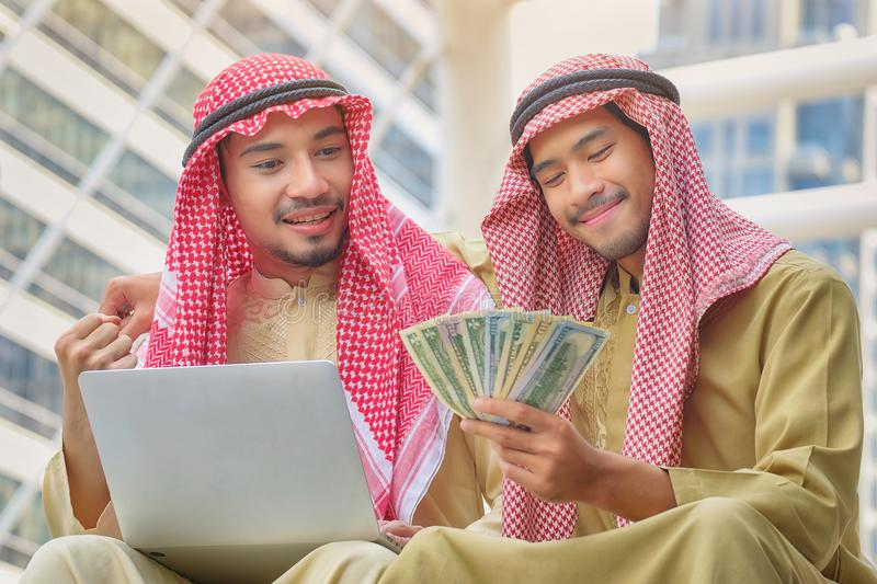 Two Arab businessmen rejoice in the success of their business ventures. Happy with the money received royalty free stock images