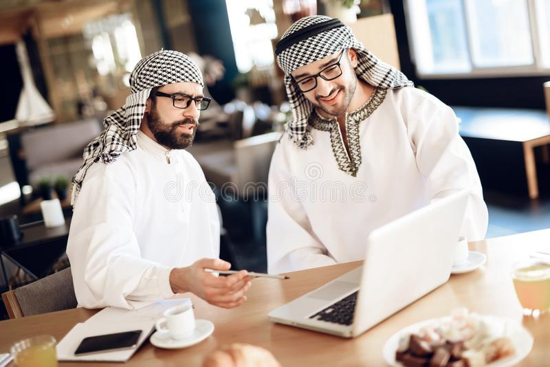 Two arab businessmen at table at hotel room with one pointing at laptop. stock photography