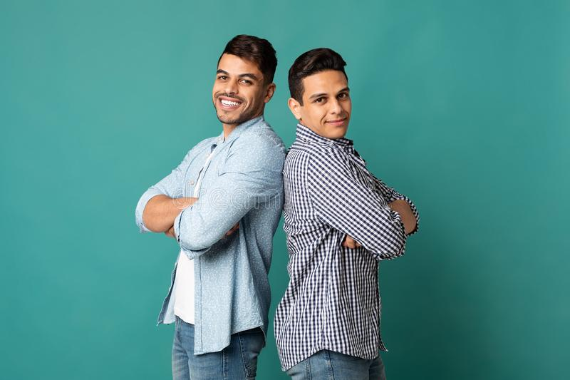 Two Arab Male Friends Standing Back-To-Back Over Turquoise Background royalty free stock photos