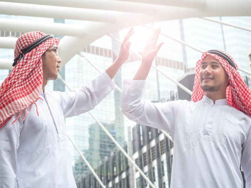 Two Arabic muslim wear white shirt humble say hello in the morning on cityscape background stock photography