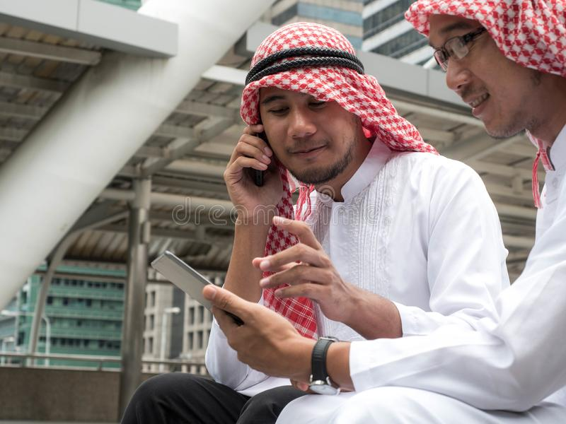 Two Arabic muslim wear white shirt humble sitting at front modern office discussing work with tablet and use the smartphone royalty free stock photos