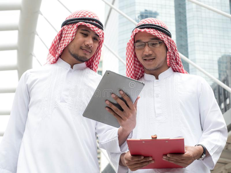 Two Arabic muslim wear white shirt humble Standing at front modern office discussing work with tablet royalty free stock photos