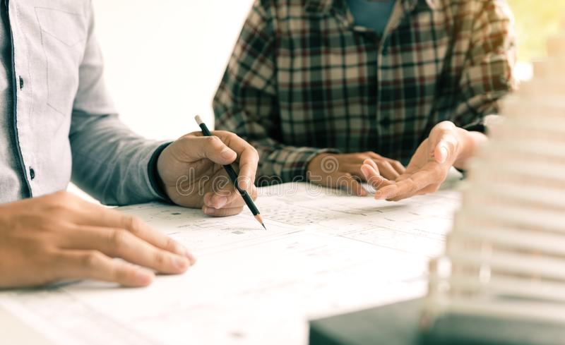 Two architect people sitting and presents plan on blueprints. royalty free stock images