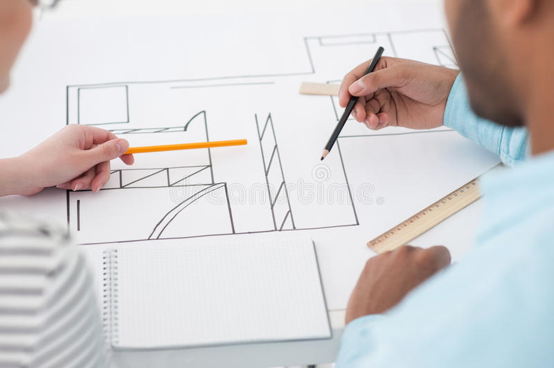 Two architects discussing details of blueprint royalty free stock image