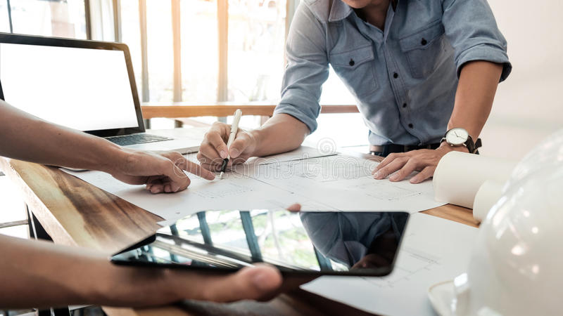 Two Architects engineer discussing data working and tablet, lap. Top with blueprint - Closeup on hands and project print royalty free stock images