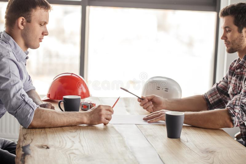 Two architects are having fun with a pen and a pencil while drinking royalty free stock image