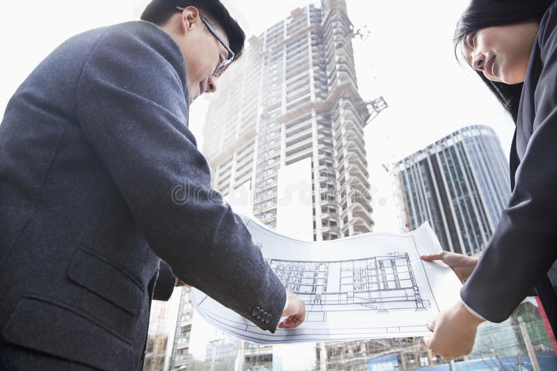 Two architects looking at blueprint at a construction site stock images