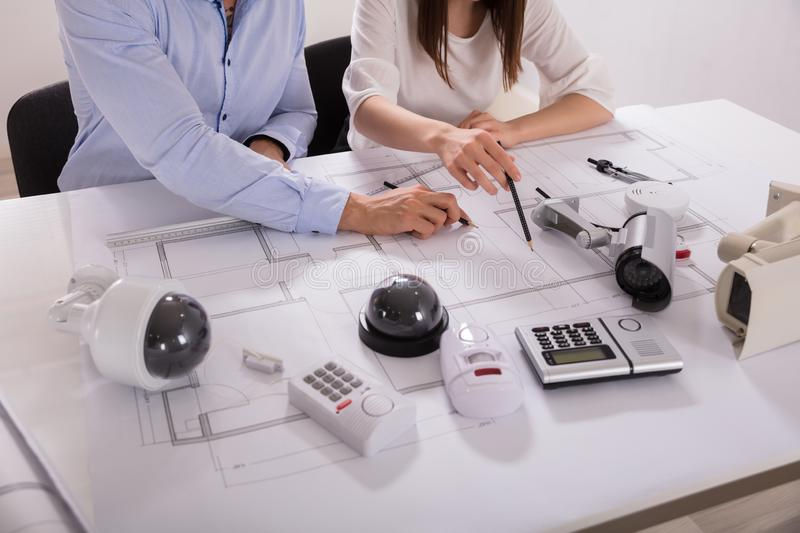 Two Architects Planning Project On Blueprint royalty free stock image