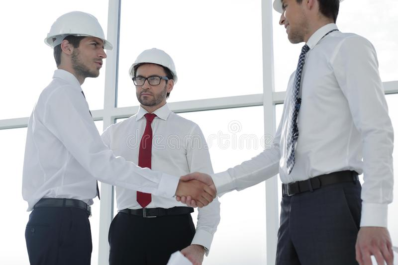 Two architects shaking hands after a meeting in office. Concept of cooperation stock photos