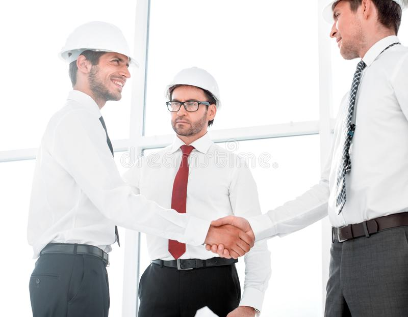 Two architects shaking hands after a meeting in office. Concept of cooperation royalty free stock images