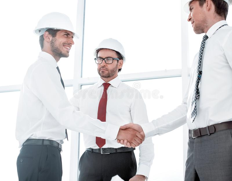 Two architects shaking hands after a meeting in office. Concept of cooperation royalty free stock photography