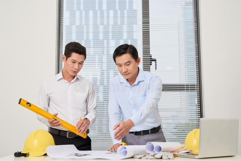 Two architects standing at a desk and discussing a project stock images