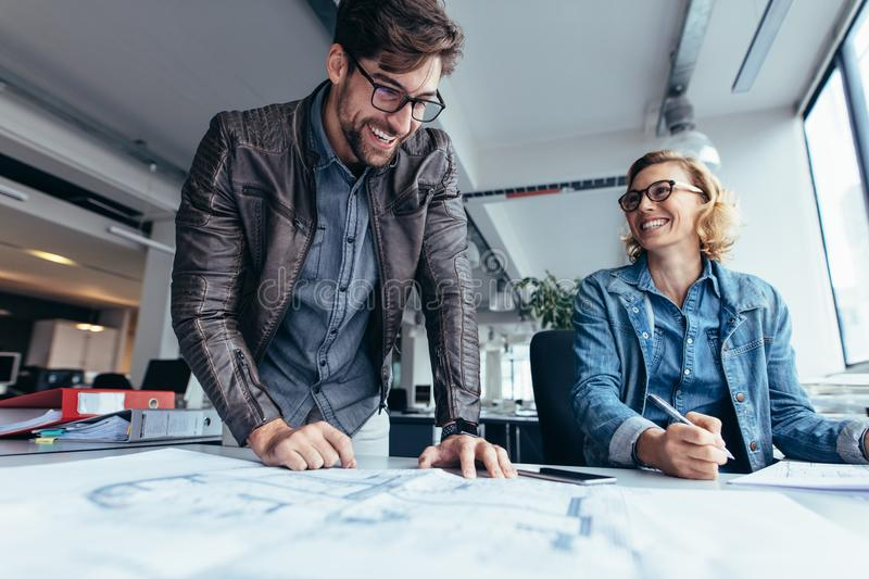 Two architects working on construction plan royalty free stock photo