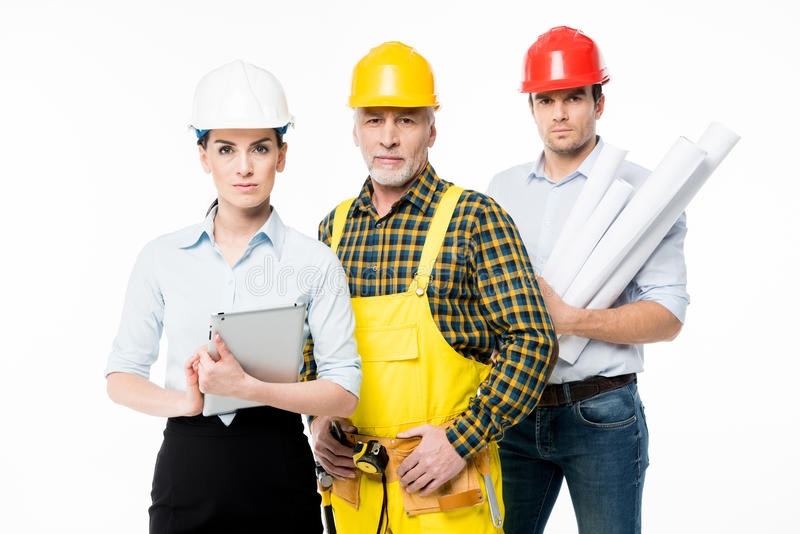 Two architects and workman. Two architects and mature workman looking at camera on white royalty free stock photos
