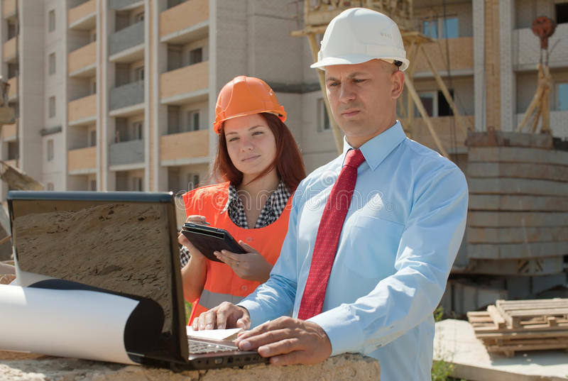 Two architects works in front of building site. Two architects wearing protective helmet works in front of building site royalty free stock photo
