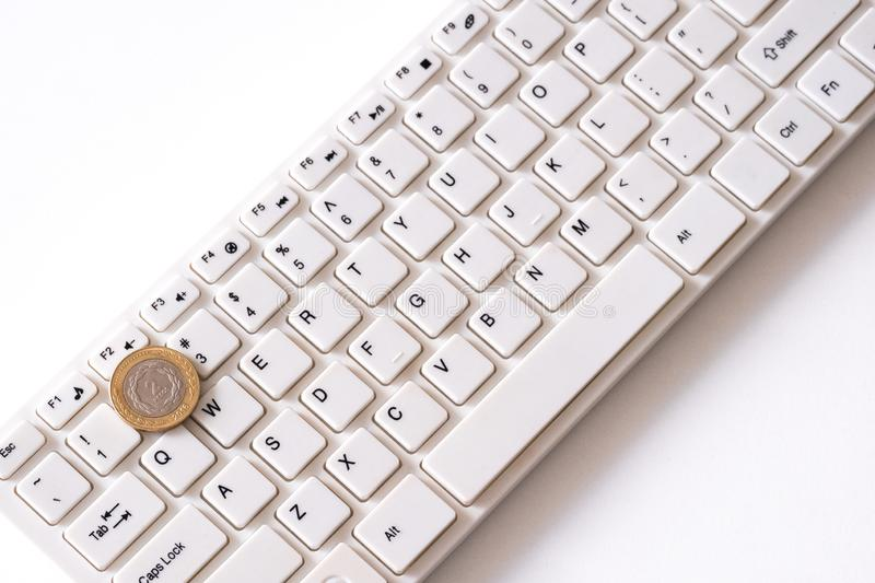 Two argentinian peso coin on white keyboard background. White background. Concept of finance and computer technology. How to make stock photos