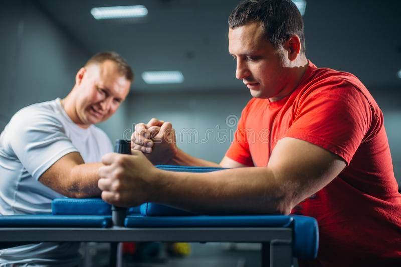 Two arm wrestlers fighting on their hands. At the table with pins, battle in action, wrestling competition. Wrestle challenge, power sport stock photo