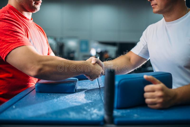 Two arm wrestlers shake hands after battle. Or wrestling competition, gym interior on background. Wrestle challenge, power sport royalty free stock photography