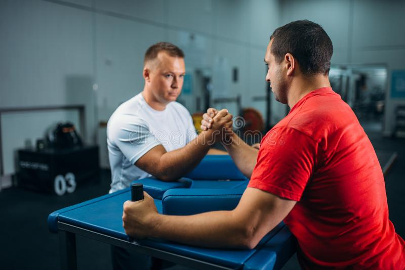 Two arm wrestlers at the table with pins, training. Before wrestling competition. Wrestle challenge, power sport stock photo