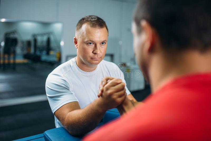 Two arm wrestlers at the table with pins, training. Before wrestling competition. Wrestle challenge, power sport stock photography