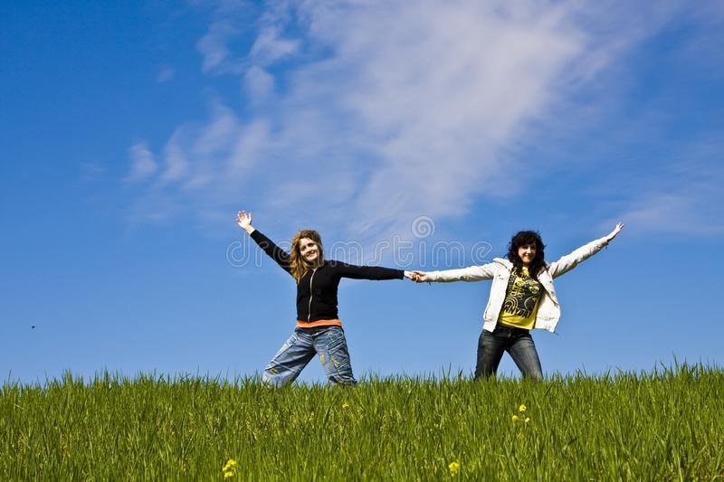 Two arms raised friends in a meadow stock image