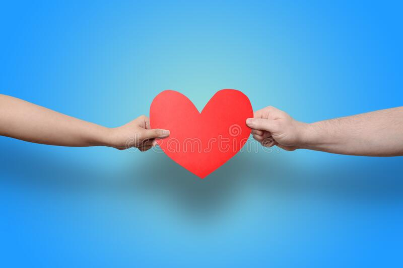 Two hands holding heart, red paper cut out love royalty free stock photo