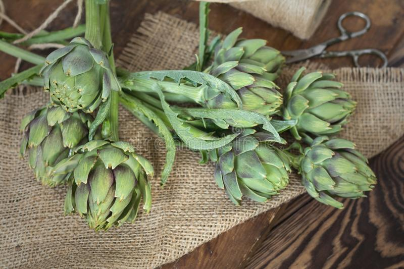 Two artichoke bouquets on sackcloth on wooden background. Top vi. Ew royalty free stock photos