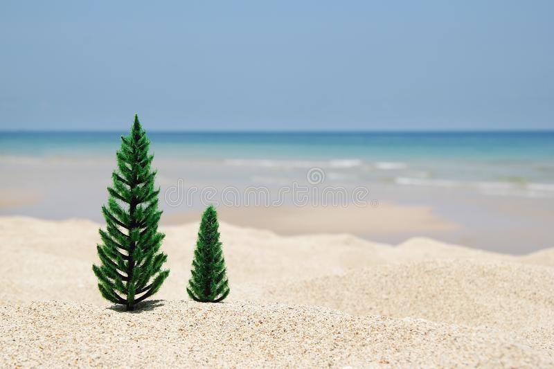 Two artificial Christmas trees on a sandy beach on the background of blue sea and sky. stock images
