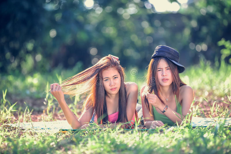 Two Asia young women lying on grass royalty free stock photography