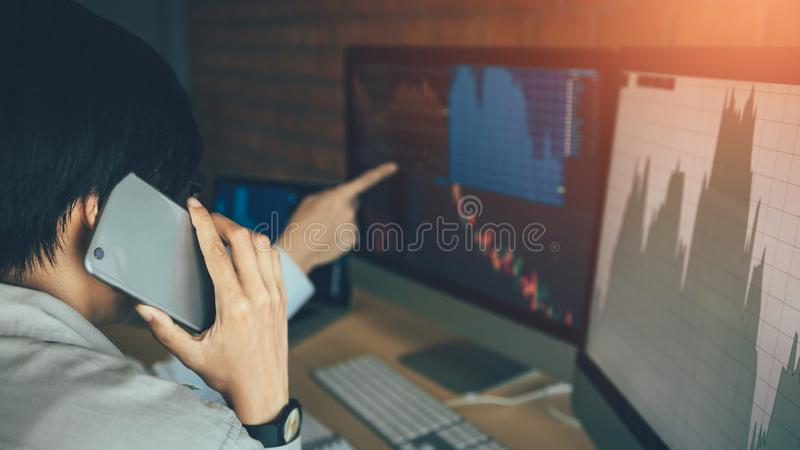 Two asian agent man working and analysis together in office  market financial charts and graphs and calling to customer royalty free stock photography