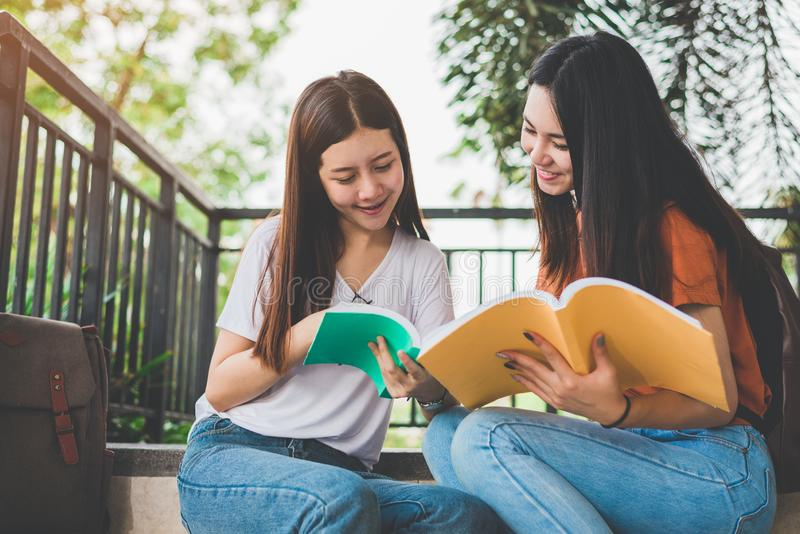 Two Asian beauty girls reading and tutoring books for final examination together. Student smiling and sitting on stair. Education stock photo