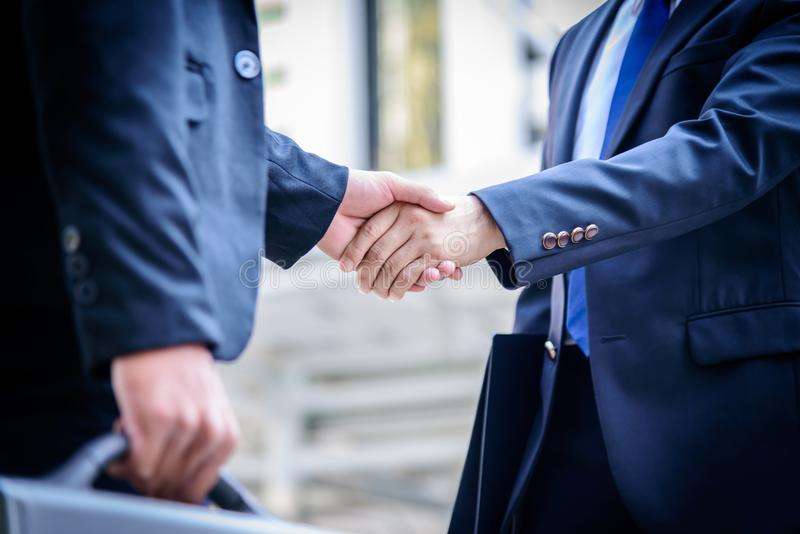 Two asian business have handshake with building and city background. stock image