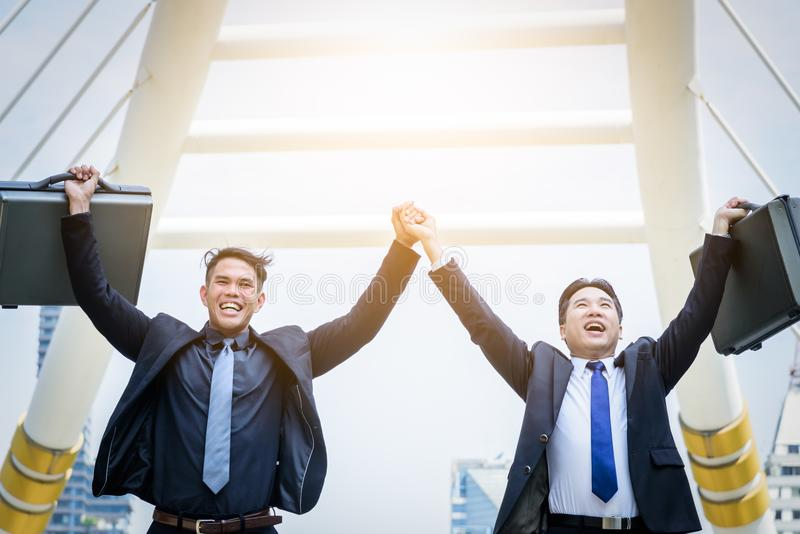 Two asian business have victory of business goal with building a. Nd city background royalty free stock image