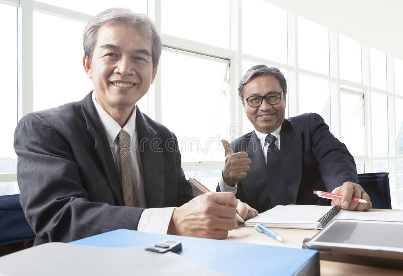 two of asian business man toothy smiling face ,relaxing in office life royalty free stock photos