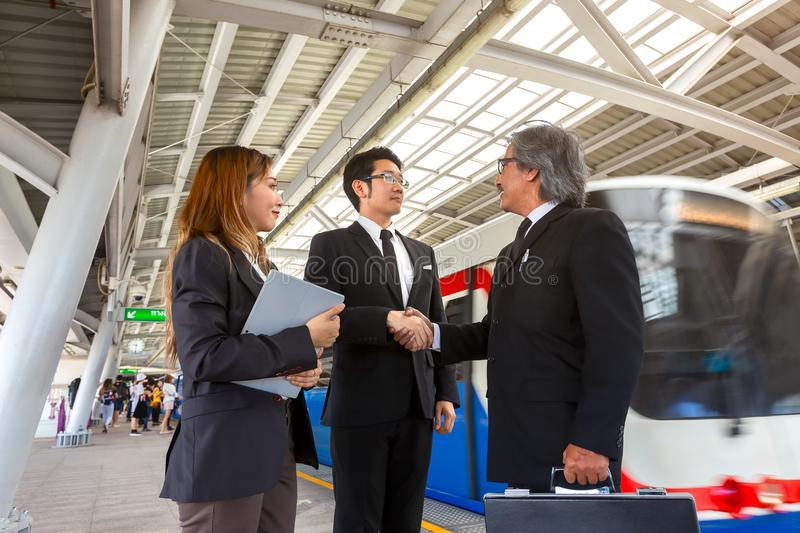 Two Asian business partner shaking their hands in sky train stat stock photos