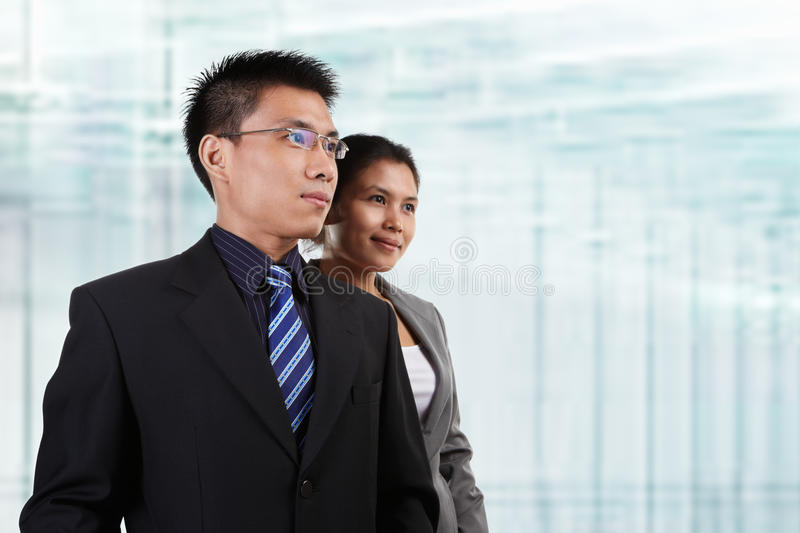 Two Asian business people. Pose together with blur glass windows as background royalty free stock image