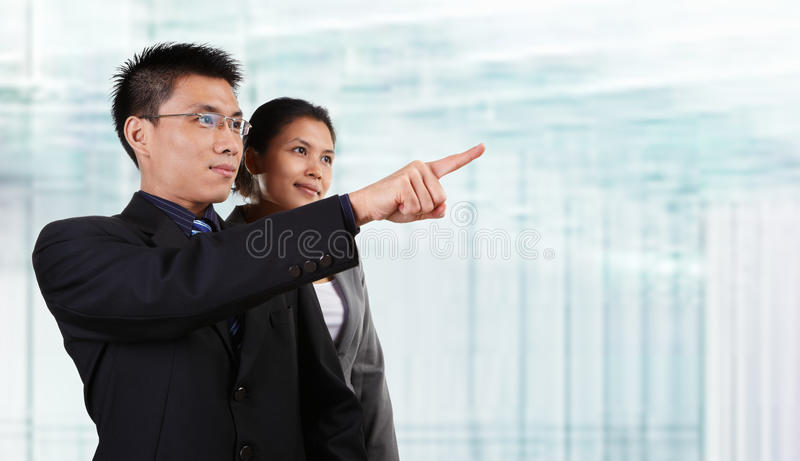 Two Asian business people. Pose together and the male pointing away his hand, with blur glass windows as background royalty free stock image